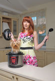 Red haired woman with new multicooker and small dog Royalty Free Stock Image
