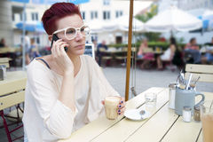 Red-haired woman outside talking on the phone. Red-haired woman sitting outside and talking on the phone Royalty Free Stock Images