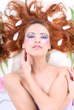 Red-haired woman with petals lying Royalty Free Stock Photography
