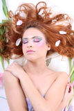 Red-haired woman with petals lying Stock Photography