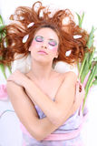 Red-haired woman with petals lying Royalty Free Stock Image
