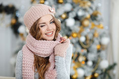 A red-haired woman in the pink hat near Christmas tree Stock Images