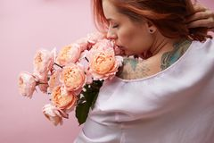 Red-haired woman with pink roses. Beautiful pink roses of a media on a shoulder of a red-haired girl on a pink background. Valentine`s Day, Mother`s Day Stock Image