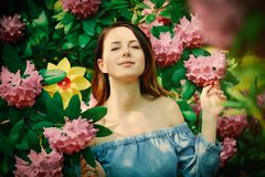 Woman with pinwheel in blossom garden royalty free stock photography