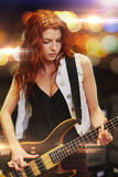 Red haired woman playing guitar on stage Royalty Free Stock Photography