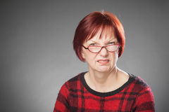 Red-haired woman, portrait, facial expression, citical, wrinklin. G nose, studio portrait on gray Royalty Free Stock Photo