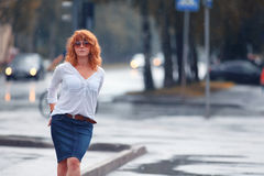 Red-haired woman in the rain. Portrait of red-haired happy woman in the rain Stock Photos