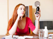 Red-haired woman reading about medications in manual at home Stock Images