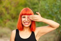 Red haired woman covering her eyes in a park Stock Photos