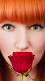 Red-haired woman with a rose on her mouth Stock Photos