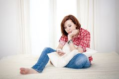 Red haired woman sad, worried sending a message on her mobile cell phone Stock Image