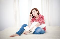 Red haired woman sad, worried talking on her cell mobile phone Royalty Free Stock Image