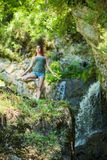 Red-haired woman in shorts doing yoga at the waterfall. A girl stands in a pose of a tree in the forest royalty free stock photos