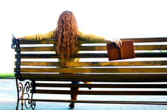 Red - haired woman sitting on bench with book Royalty Free Stock Images