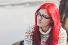 Red-haired woman sitting near the river Royalty Free Stock Images