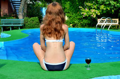 Red-haired woman sitting by the pool in the lotus position, seen Royalty Free Stock Images