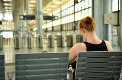Red haired woman sitting in the station waiting Stock Image
