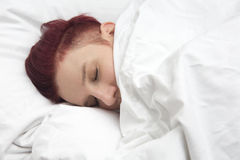 Red-haired woman sleeping in bed Stock Photos