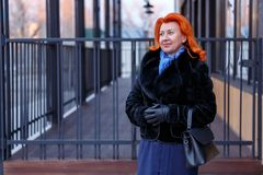A woman in a fur coat is holding her hands together in the street on a blurred background. A red-haired woman with a slight smile is looking away. In a fur coat Royalty Free Stock Images