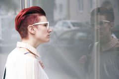 Red-haired woman standing in front of a window Royalty Free Stock Images