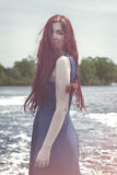 Red-haired woman standing in the river Stock Photos