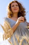 Red-haired woman standing in wheat field Royalty Free Stock Photos