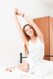 Red-haired woman stretching on white pillow in bed at home Stock Photos