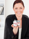 Red-haired woman in suit holding a miniature hous Stock Image