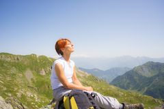 Red haired woman sunbathing on the mountain top Stock Images