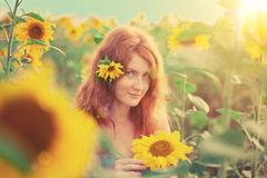 Red-haired woman with sunflowers Stock Images