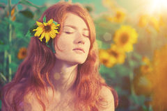 Red-haired woman with sunflowers Royalty Free Stock Images