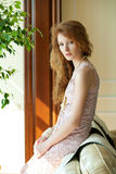 Red-haired woman in the sunlight. Red-haired woman in the sun sitting on the sofa in the interior Stock Images