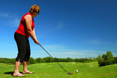 Red-Haired Woman Tees Off. A woman tees off on a beautiful sunny day. Plenty of copy space in the sky Royalty Free Stock Image