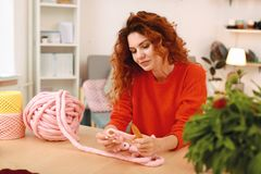 Red-haired woman thinking about knitting present for cousin. Present for cousin. Red-haired appealing woman feeling inspired while thinking about knitting Stock Photography