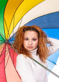 Red-haired woman with  umbrella. Young red-haired woman with a color umbrella Royalty Free Stock Photography