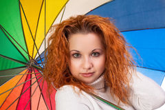 Red-haired woman with  umbrella. Young red-haired woman with a color umbrella Stock Photos