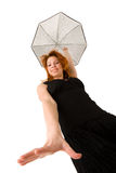 Red haired woman with umbrella looking down. Red haired woman in black dress with umbrella looking down Royalty Free Stock Images