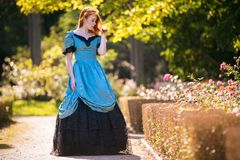 Red-haired woman in Victorian dress. With autumn park stock image