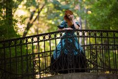 Red-haired woman in Victorian dress. With autumn park royalty free stock images