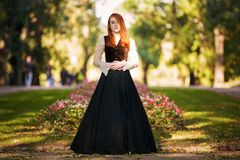 Red-haired woman in Victorian outfit. With autumn park royalty free stock photo