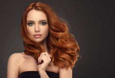 Red haired woman with voluminous, shiny and curly hairstyle. Frizzy hair.