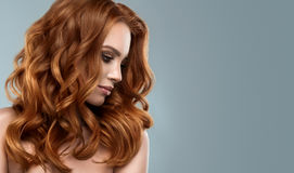 Red haired woman with voluminous, shiny and curly hairstyle.Frizzy hair. stock image