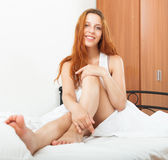 Red-haired woman waking in her bed with white sheets Stock Photography