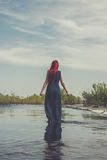 Red-haired woman walking in the river Stock Image