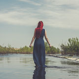 Red-haired woman walking in the river Royalty Free Stock Photography