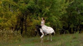 Red-haired woman in wedding dress riding galloping horse near wood