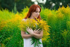 Red haired woman with yellow flowers stock photos