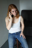 Red Haired Woman in White Tank Top Talking on Cell Phone Royalty Free Stock Image