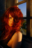 Red haired woman at window Stock Photography