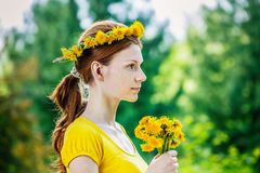 Red-haired woman with wreath and bouquet of dandelions Stock Photos
